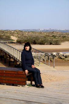 Woman Sitting Next To A Bridge Royalty Free Stock Image