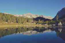 Free Calm Lake Surface Mirroring Forest Trees And Mountain Ranges At Daytime Stock Photography - 86694962