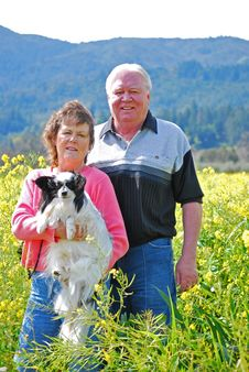 Portrait Of A Happy Couple With Their Dog Stock Photography