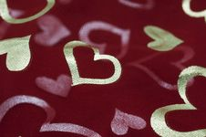 Golden Hearts On Dark Red Mesh Stock Photo