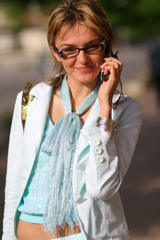 Young Woman Walking On The Street And Talking On The Phone Royalty Free Stock Photography