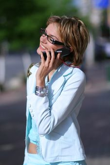 Young Woman Walking On The Street And Talking On The Phone Stock Image