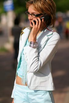 Young Woman Walking On The Street And Talking On The Phone Stock Photo