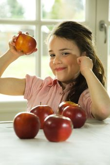 Brown Haired Child Presenting An Apple Royalty Free Stock Images