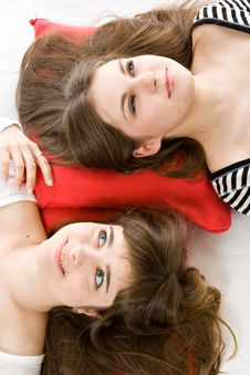 Two Girls Lying On Red Pillow Stock Image