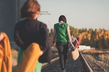 Free Woman Wearing Green Dress Holding Basket Walking Center Of Train Rail During Day Time Royalty Free Stock Images - 87314959