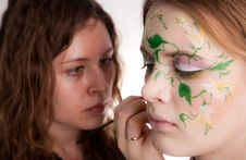 An Artist Making The Flower Tattoo On The Face Of Stock Photography
