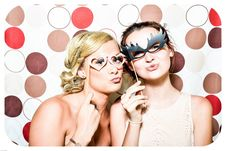 Free Two Woman Taking Photo In Photobooth Holding Black And Pink Masquerade Mask Stock Images - 87587654
