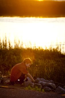 Little Boy Exploring At Sunset Stock Photo