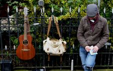 Free Man Leaning Against Black Steel Fence Beside White And Brown Sling Bag And Brown Acoustic Guitar Royalty Free Stock Photos - 87719768