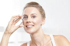 Free Caucasian Brunnete Curling Her Eyelashes Stock Image - 8787431