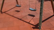 Free Swings-casting-shadow-on-playground Stock Photography - 87858572