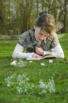 Free Girl Reading Book On Grass In Park. Royalty Free Stock Photography - 8797467