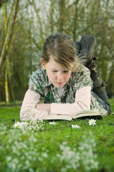 Girl Reading Book On Grass In Park. Stock Image