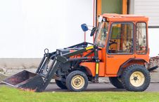 Orange Tractor With Scoop Bucket In The Suburbs