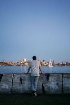Free Person Standing And Leaning On Concrete Wall Facing Ocean And Skyline At Dawn Stock Images - 88036924