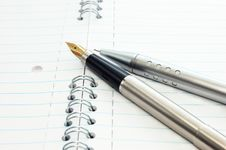 Free A Gold Pen And Mechanical Pencil On A Notepad Stock Photos - 8832073