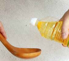 Pouring Oil Into Wooden Spoon Stock Photo