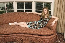 Free Young Attractive Female Smiling On Couch Royalty Free Stock Photos - 8859668