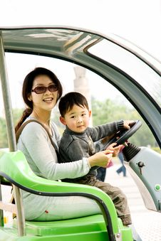 Boy And Mother Driving Electromobile Royalty Free Stock Photography
