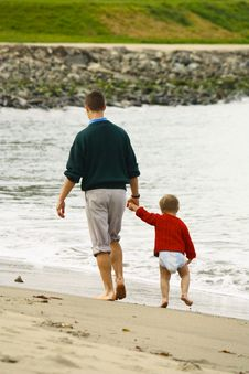 Big Brother Walking Little Brother On Beach Stock Image