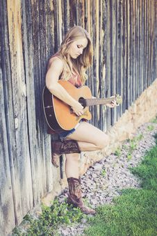 Free Woman Playing Guitar While Leaning On Wood During Daytime Royalty Free Stock Image - 88626326