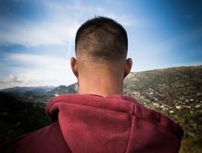 Free Man In Red Hoodie Standing On Mountain Under Blue And White Sunny Cloudy Sky Stock Photos - 88627053