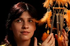 Young Brunette And Wind Chime Royalty Free Stock Photos
