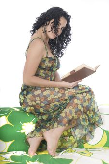 Woman Reading A Book Sitting On An Armchair Stock Photo