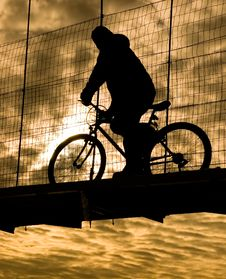 Biker On Suspension Bridge Royalty Free Stock Photography