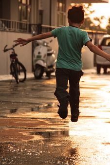 Free Boy In Green T Shirt Running On Wet Road During Daytime Royalty Free Stock Photo - 89058355