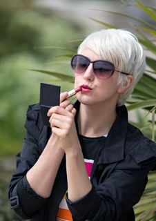 Free Blond Short Haired Woman Applying Pink Lipstick Outside Royalty Free Stock Images - 89129589