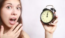 The Girl And An Alarm Clock. Stock Photo