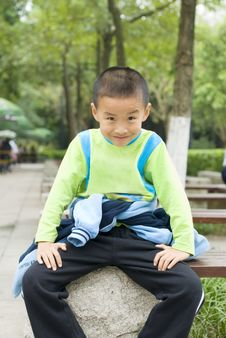 A Kid Sit Beside Tree Stock Photo