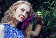 Free Woman Wearing Blue Floral Sleeveless Dress Smelling Violet Flower Stock Photos - 89570193