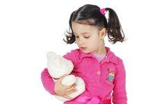 Little Girl Hugging A Teddy Bear Stock Image