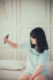 Free Girl In Blue Crew Neck Shirt Using Her Mobile Phone Indoors Stock Photography - 89635772