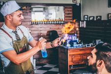 Free Man In Green Apron Spraying The Flaming Pen In Front Of The Man Stock Photo - 89692160