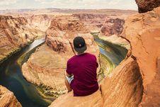 Free Man Sitting On Brown Rock Formation Stock Image - 89804161