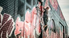 Free Man In Gray Shirt Standing On Gray Steel Ladder Painting Black White And Red Graffiti On Concrete Wall Outdoors Stock Photography - 89805312