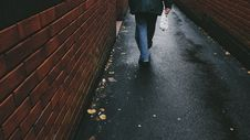 Free Person Walking On Black Asphalt Pathway Between Brown Brick Wall Royalty Free Stock Images - 89805809