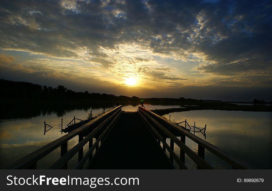 Pontoon over lake at sunset