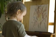 Small Girl Drawing At A Wooden Easel Royalty Free Stock Images