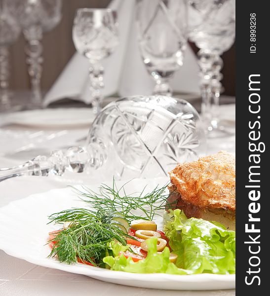 Backed meat and green salad with goblets