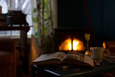 Free Book Beside White Cup On Black Table With View Of Fireplace In The Background During Daytime Stock Images - 89963514