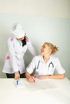 Young Doctor With Her Assistant In The Office Royalty Free Stock Images