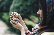 Free Woman Holding A Tiny Doll And Looking At It Stock Image - 91520191