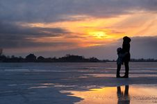 Free Mother And Child By Frozen Lake At Sunset Royalty Free Stock Images - 91758849