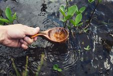Free Hand Holding Wooden Ladle Extracting Water From Stream Royalty Free Stock Image - 92128826