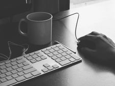 Free Hand Using Mouse At Desk With Keyboard And Cup Stock Images - 92128844